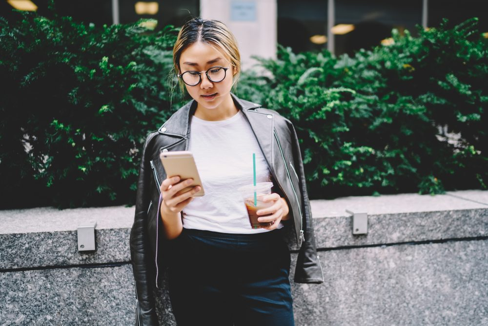 Young Chinese woman in glasses for eye protection reading news in website on smartphone connected to 4G internet. Female asian blogger chatting with followers in social networks while standing outside