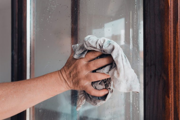 A person's hand holding an old rag while cleaning a window