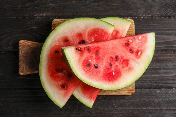 Board with juicy watermelon slices on wooden background, top view