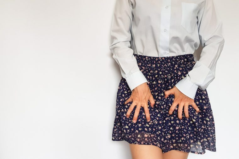 Woman clutching skirt in obvious discomfort