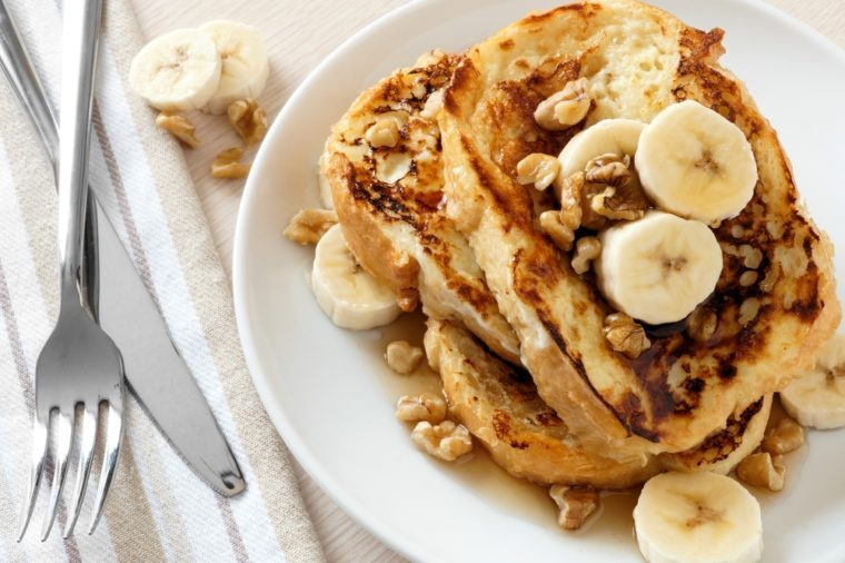 Plate of delicious French toast with bananas, walnuts and dripping maple syrup.