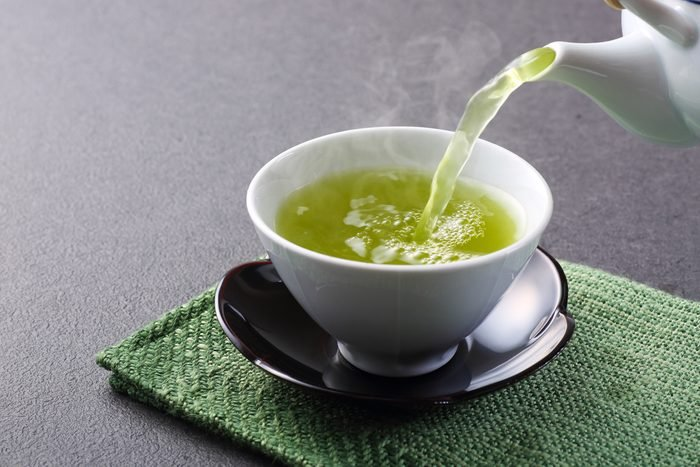 pouring cup of green tea