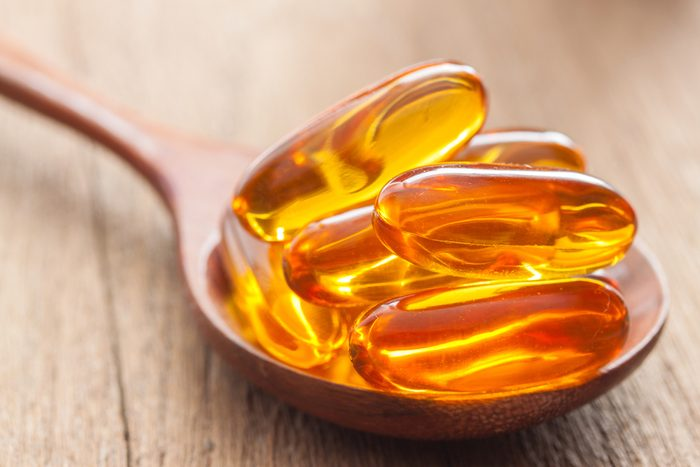 Fish oil capsules with omega 3 and vitamin D in a spoon on wooden texture, healthy diet concept,close up shot.