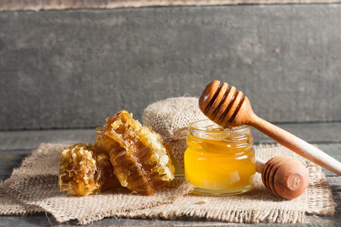 Glass jar of honey surrounded by honeycomb