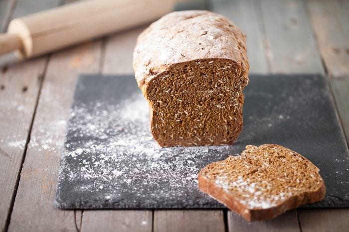 Fresh Irish soda bread with oat sliced on a slate cutting board.
