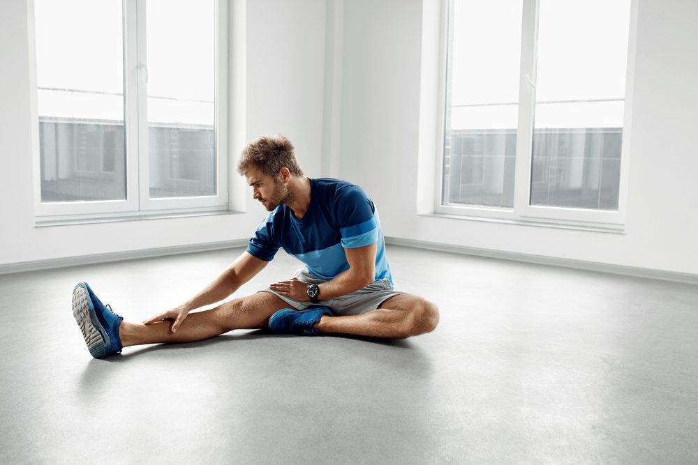 Stretch Body Exercise. Handsome Man Stretching Before Workout. Healthy Muscular Athletic Active Fitness Male Model In Fashion Sportswear Doing Stretches, Warming Up, Exercising Indoors. Sports Concept