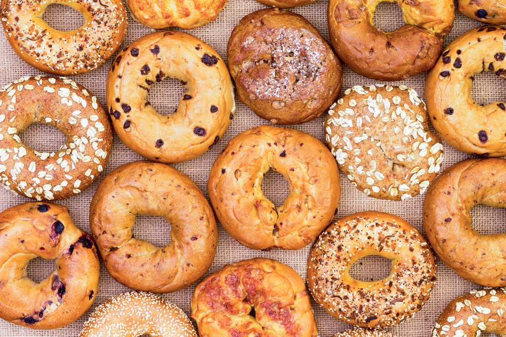 Assorted variety of different flavored freshly baked bagels in a full frame background on burlap viewed from above in an abstract pattern