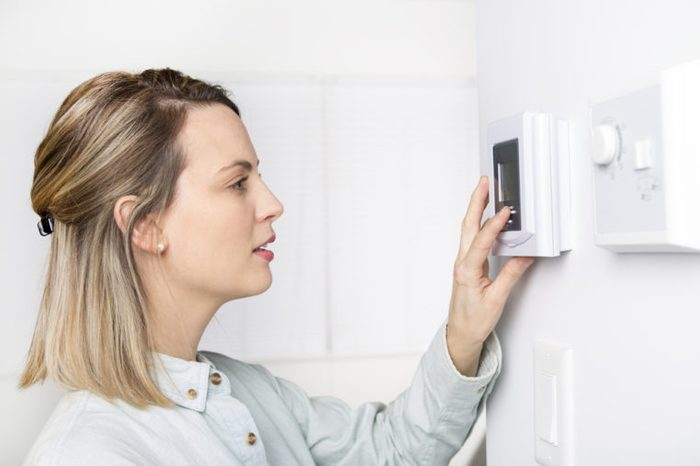 A woman setting the thermostat at a house
