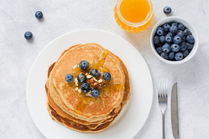 Stack of pancakes with fresh blueberries, nuts and honey on white plate.