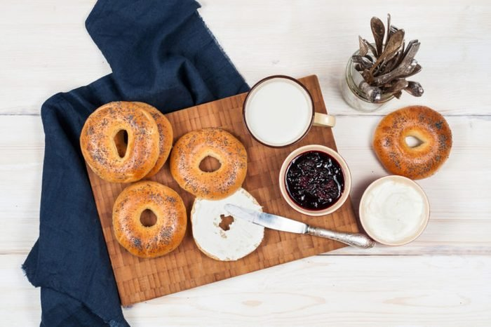 Fresh homemade Poppy bagels bread with cup of milk, cream cheese and berries jam.