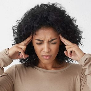 Dark-skinned young woman in beige long sleeved t-shirt frowning, having painful expressions, suffering from bad severe headache, keeping eyes closed, holding fingers on temples, trying to ease tension