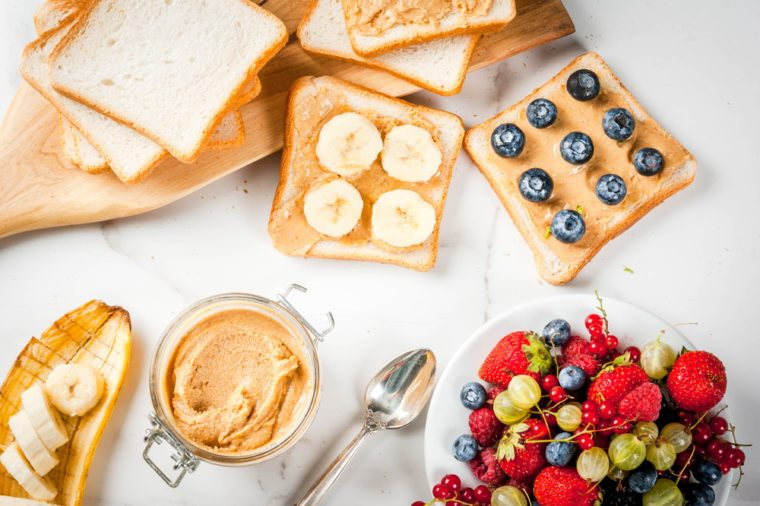 Traditional summer breakfast: sandwiches of toast with peanut butter, berry, fruit apple, peach, blueberry, blueberry, strawberry, banana on a white marble table.