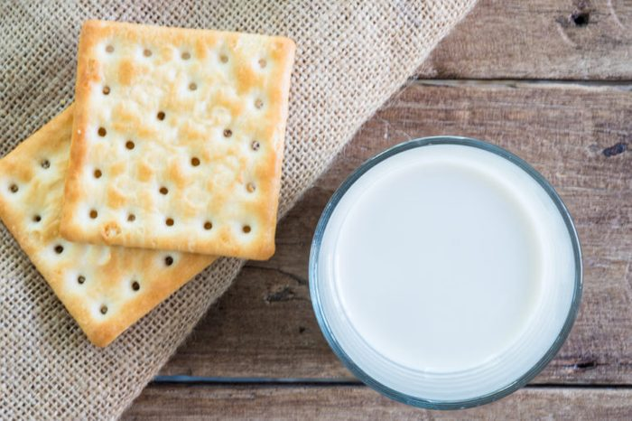 stack of crackers on gunny sack cloth on wooden table with a cup of milk, top view