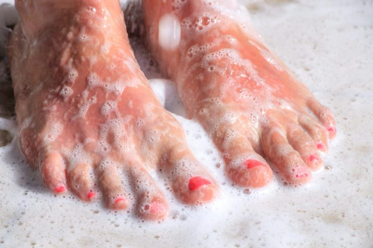 Woman's feet in the shower covered with shower gel foam