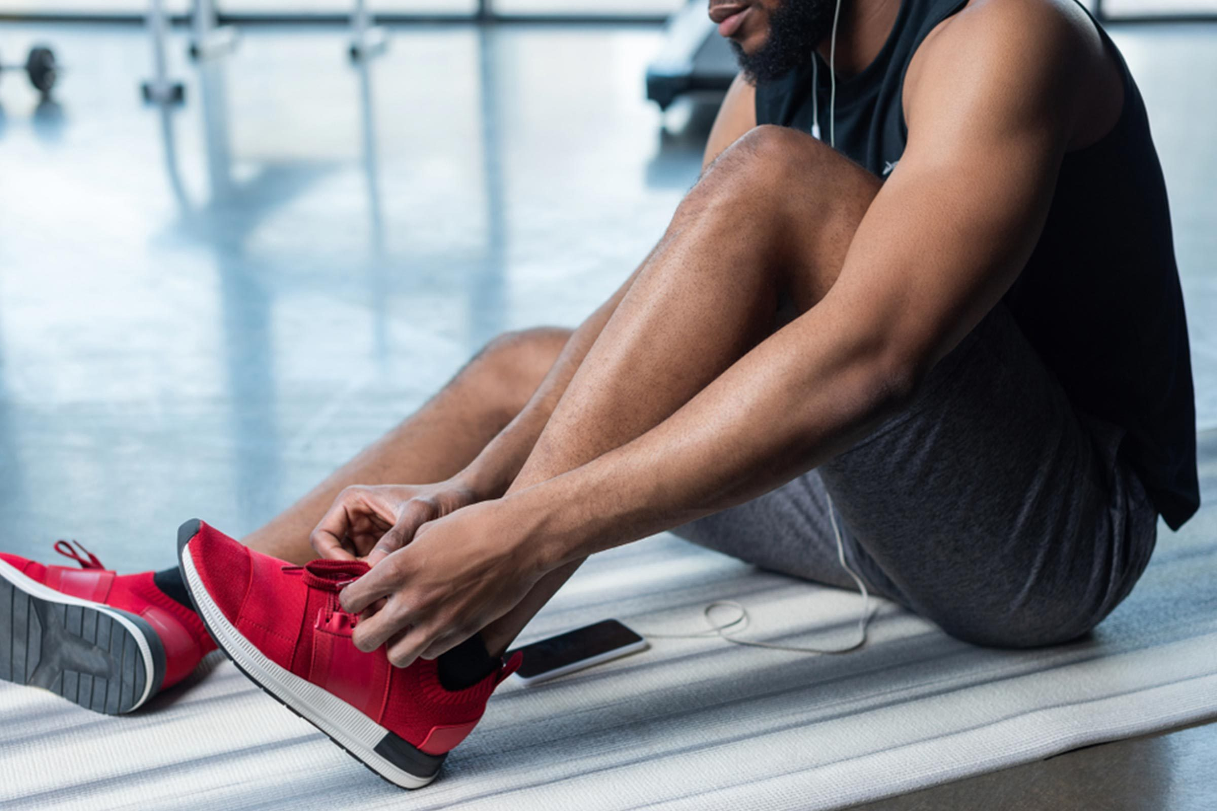 man lacing up sneakers before exercise