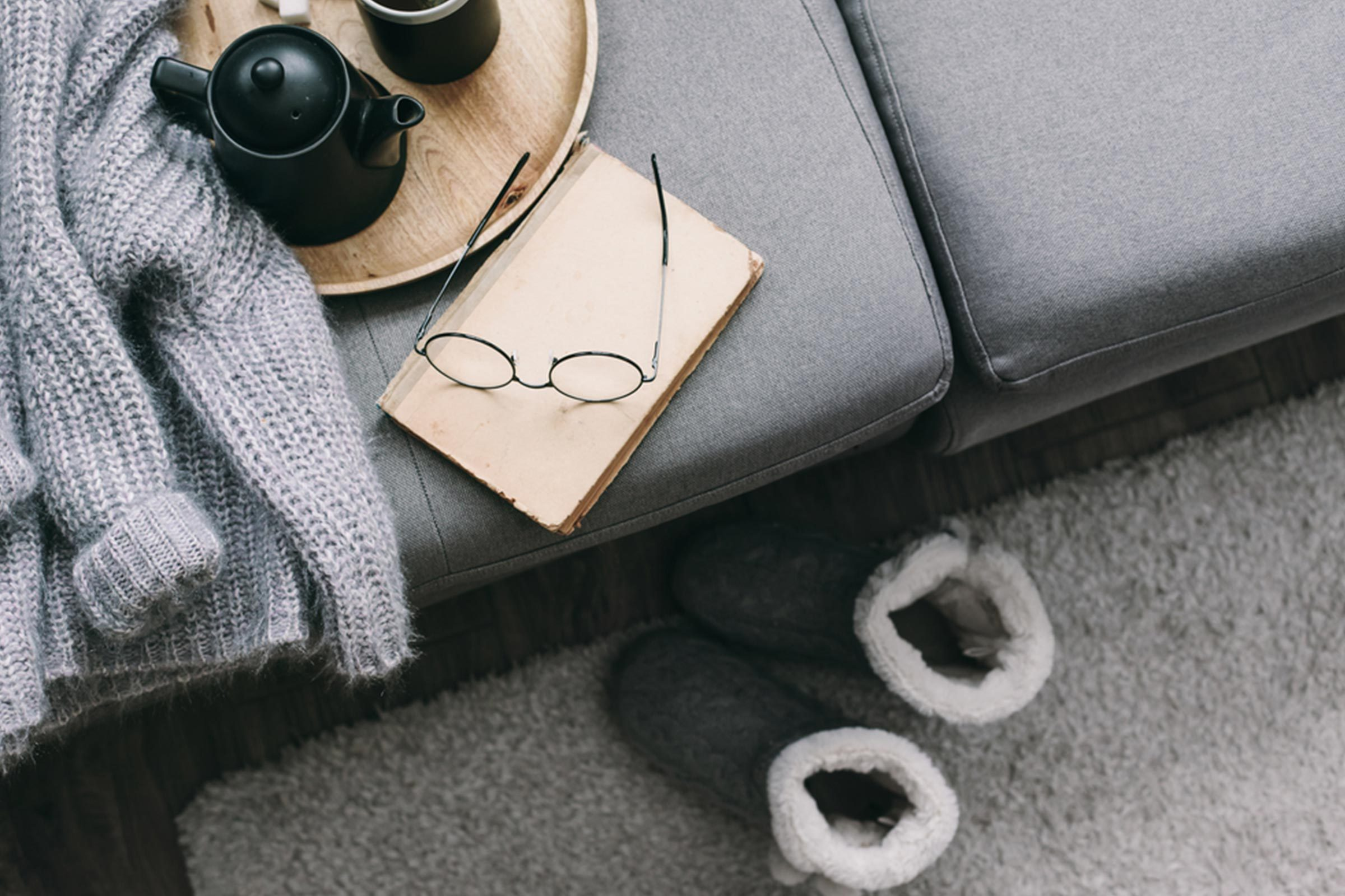 couch with glasses, slippers and journal