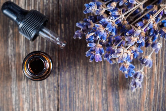 essential oil with pipette and bunch of dry lavender flowers. Top view or flat-lay. Copy space for text.