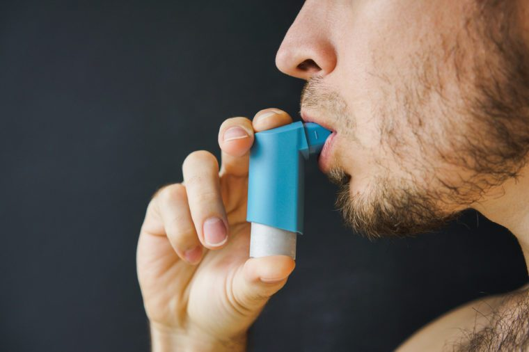 male asthmatic with an aerosol inhaler in his hand takes a breath.