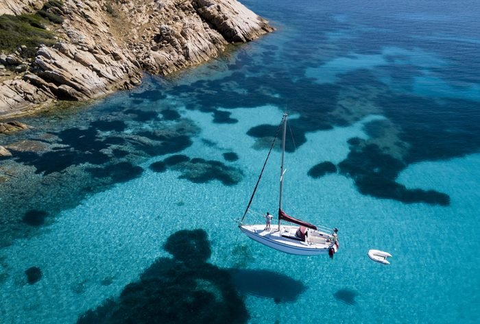 Aerial view of a boat in front of the Mortorio island in Sardinia. Amazing beach with a turquoise and transparent sea. Emerald Coast, Sardinia, Italy.