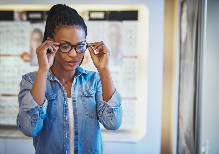 Single beautiful young African-American woman in blue shirt testing the fit for eyeglasses on her head in eye wear shop