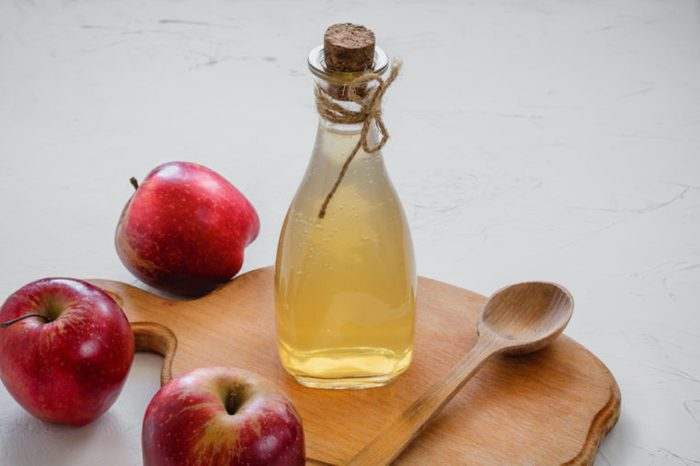 bottle of apple cider vinegar and wooden spoon on wooden board, three apples
