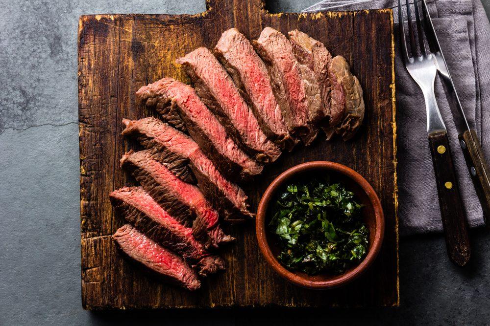 Medium rare sliced beef served on wooden board. Sliced medium rare roast beef on slate gray background