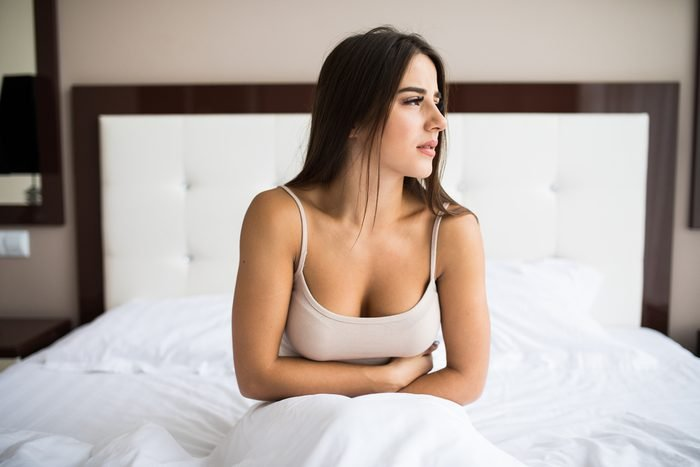 Young woman sitting on the bed with pain
