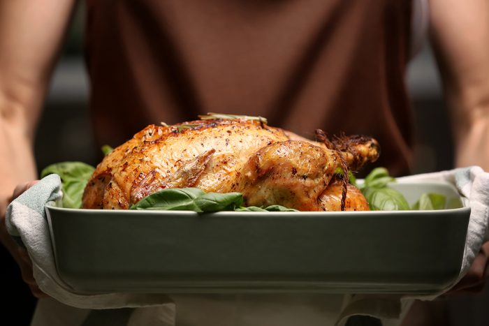 Woman holding baking dish with golden roasted turkey