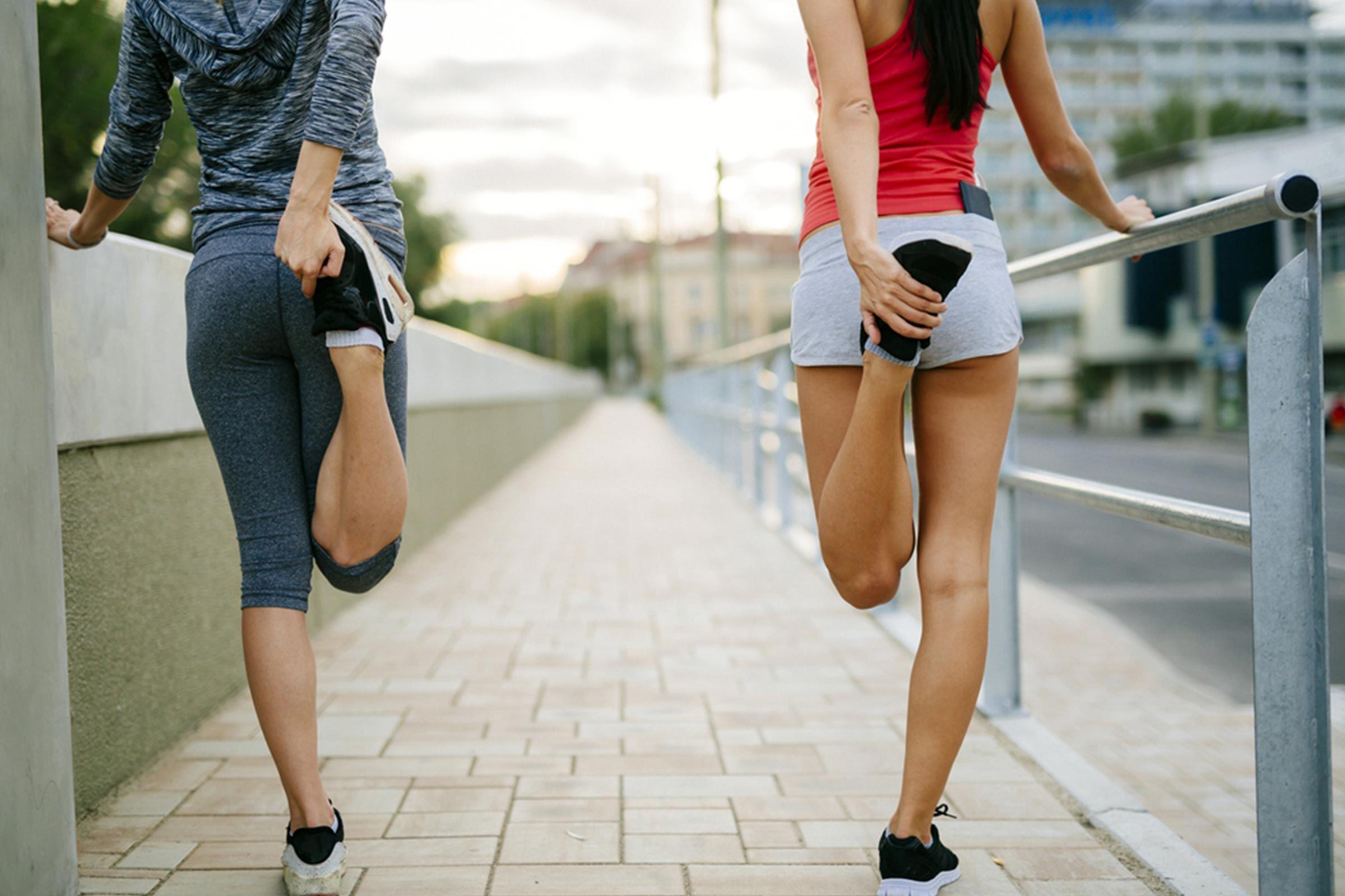 two women stretching before running