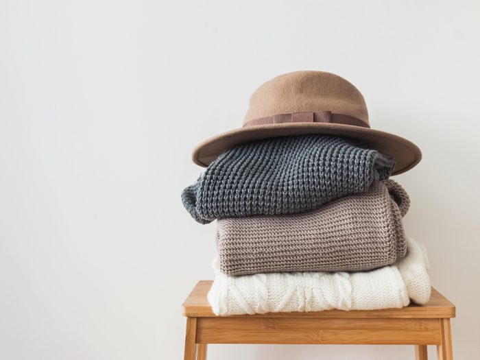 Stack of warm knitted sweater and felt hat on the top of it at the white wall background.