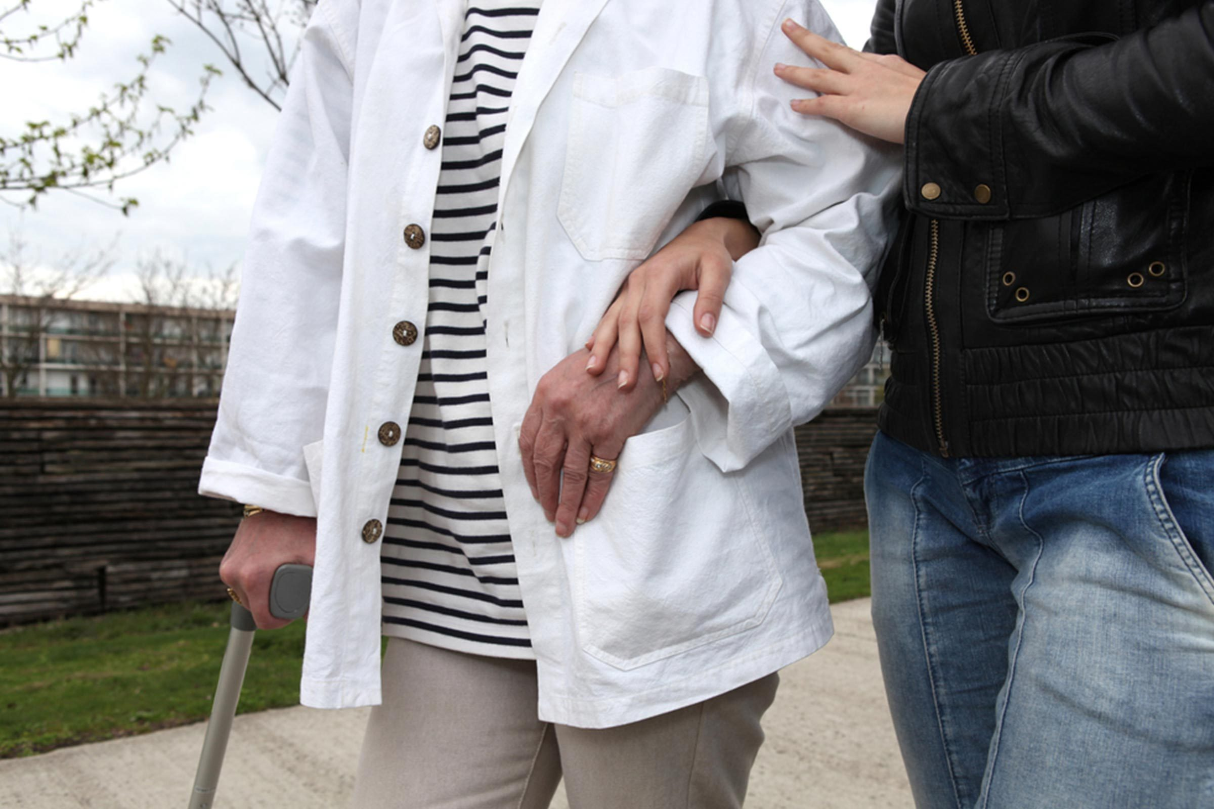 older woman walking with cane with help from friend