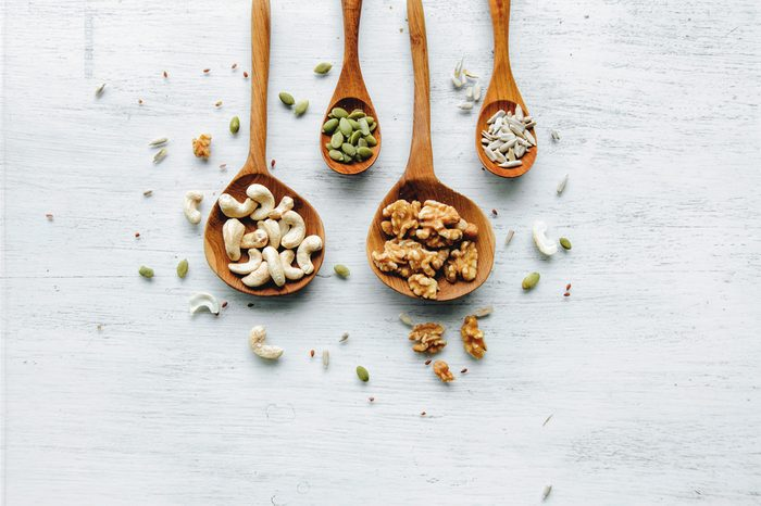 Four wooden spoons with seeds and nuts on the white table