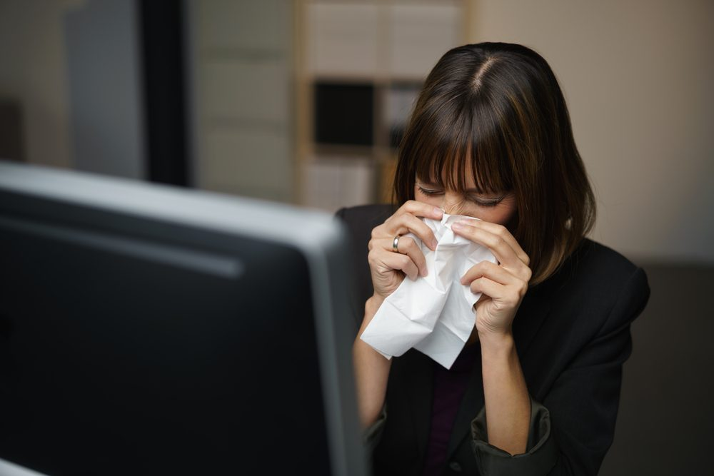woman sneezing, blowing her nose