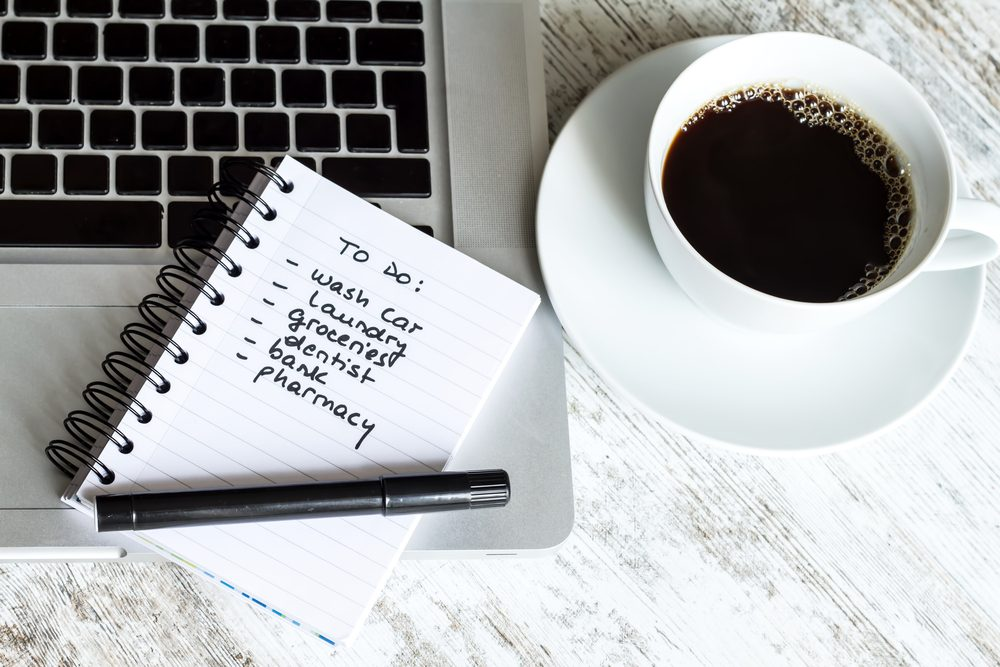 to-do list next to coffee cup and laptop
