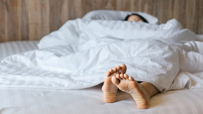 feet sticking out from under comforter in bed