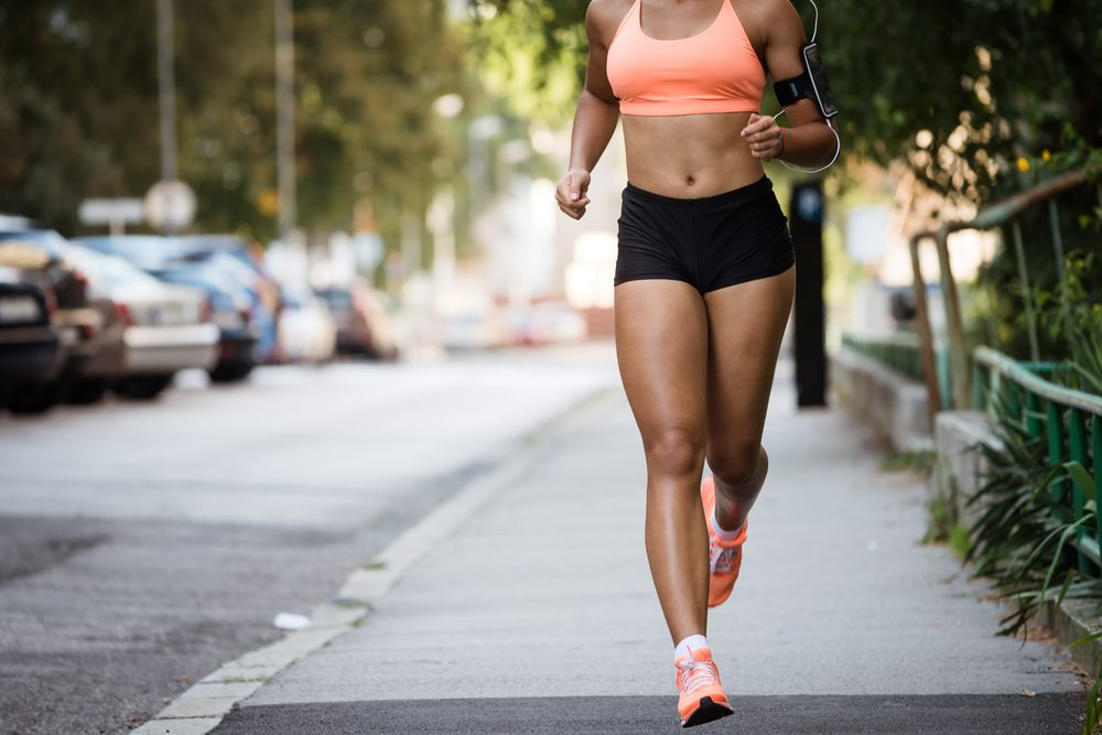 Runner listening to music while jogging on sidewalk