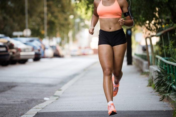Runner listening to music while jogging on sidewalk
