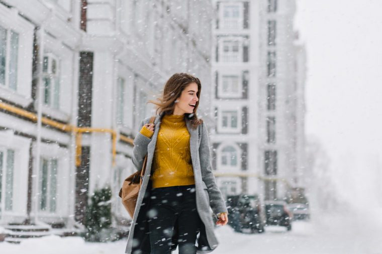 smiling young woman in coat with backpack walking in snowfall in Europe city centre. Expressing positivity, true emotions, enjoy snowing, waiting for christmas holidays, smiling to side