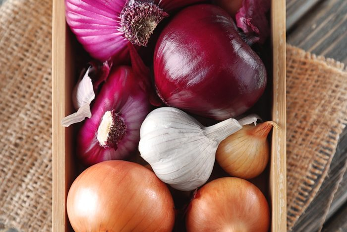 Crate with onions and garlic on table, closeup