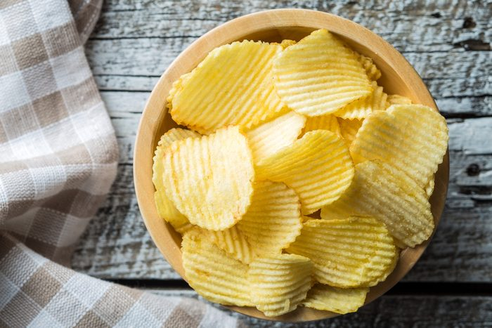 Crispy potato chips in wooden bowl. Salted potato chips. Top view.