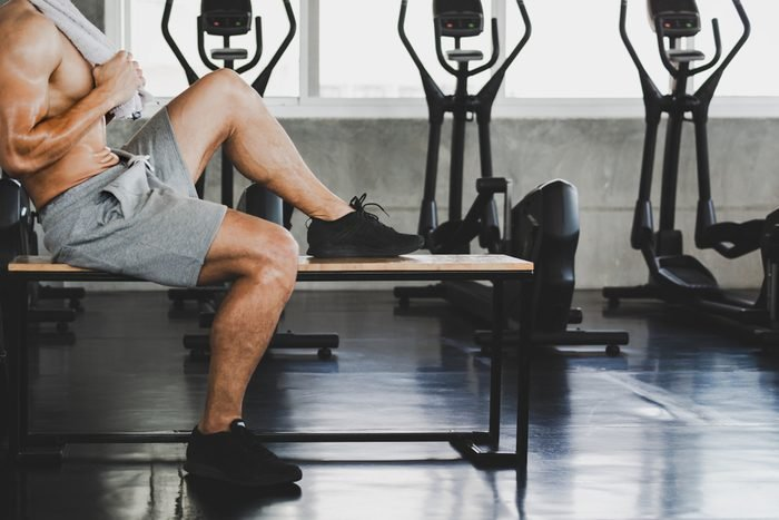 Fitness man with towel tired and resting after workout exercise in sport gym, healthy lifestyle concept