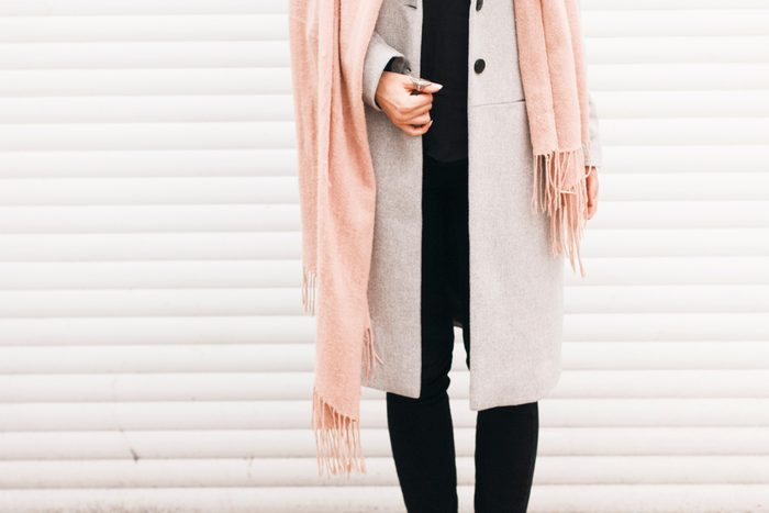 Details of everyday elegant look. Unrecognizable model wearing casual outfit. Gray coat and pink scarf in trendy minimalistic style. Street fashion for spring or fall season.