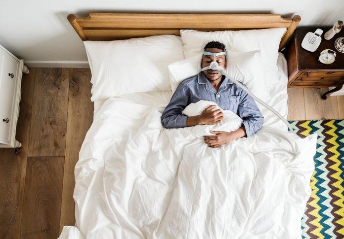 Man sleeping with an anti-snoring mask