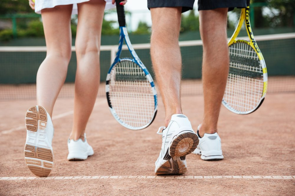 couple carrying tennis rackets