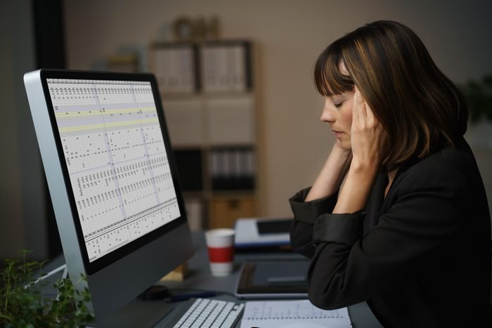 Side View of a Tired Businesswoman Working on her Computer at her Table, Holding her Head with Eyes Closed.
