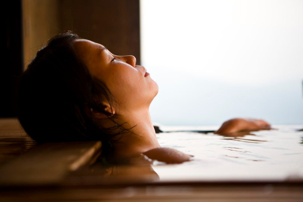 woman taking a bath relaxing and de-stressing