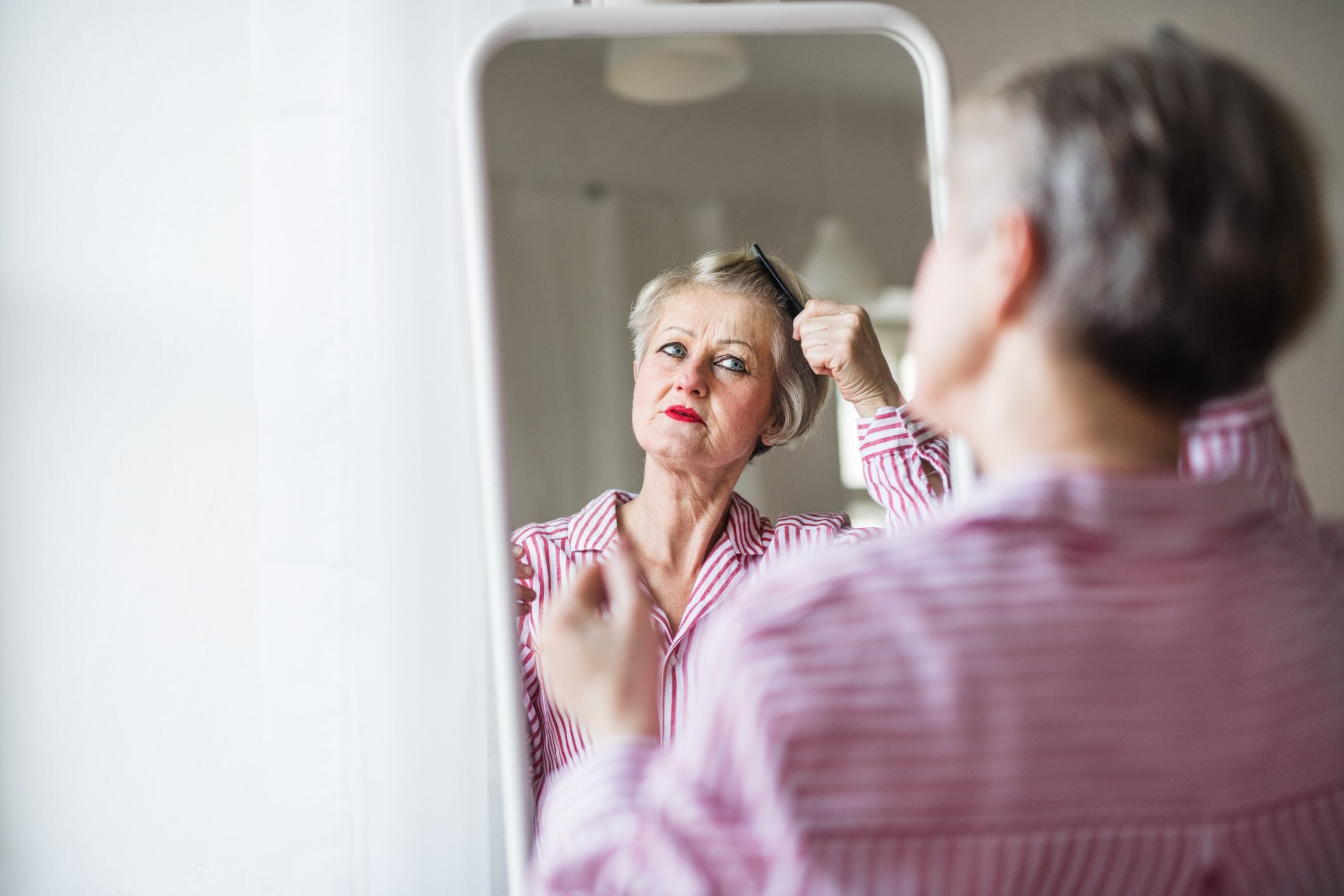 woman looking in mirror and brushing hair
