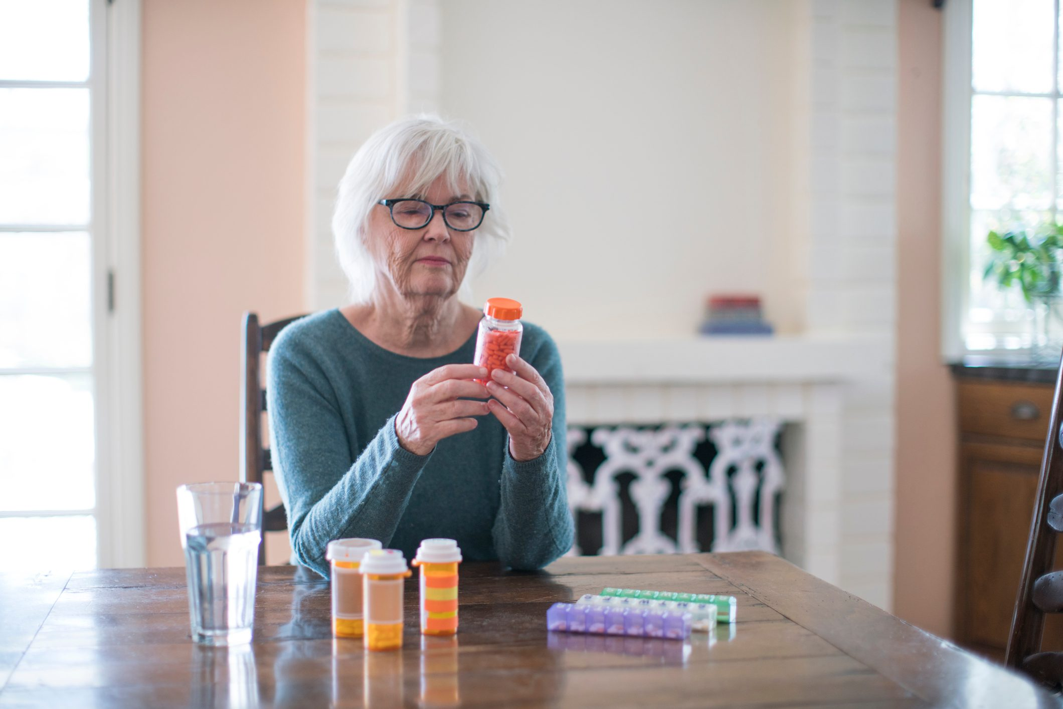 senior woman reading the label of a medication bottle