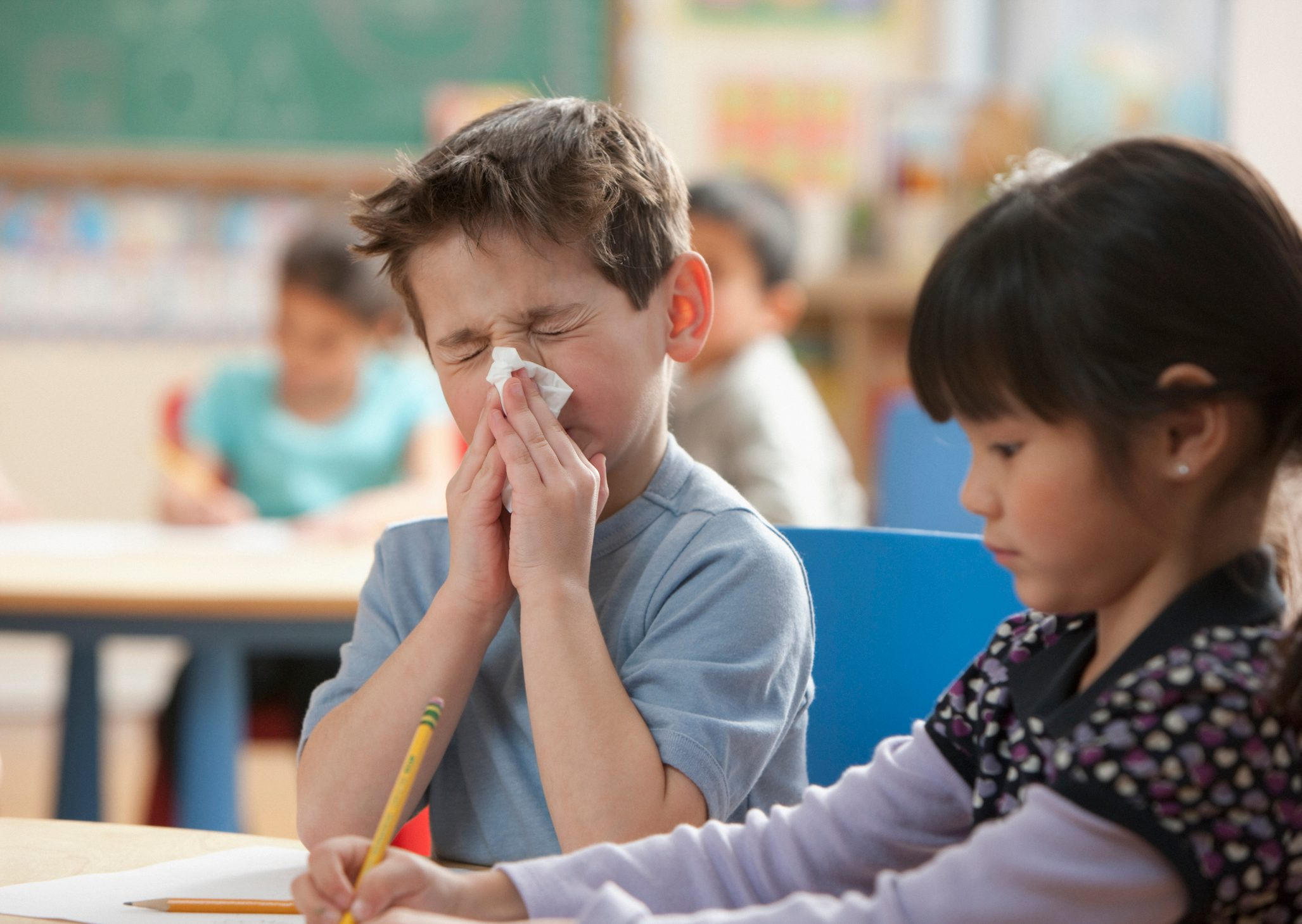 young boy blowing his nose at school