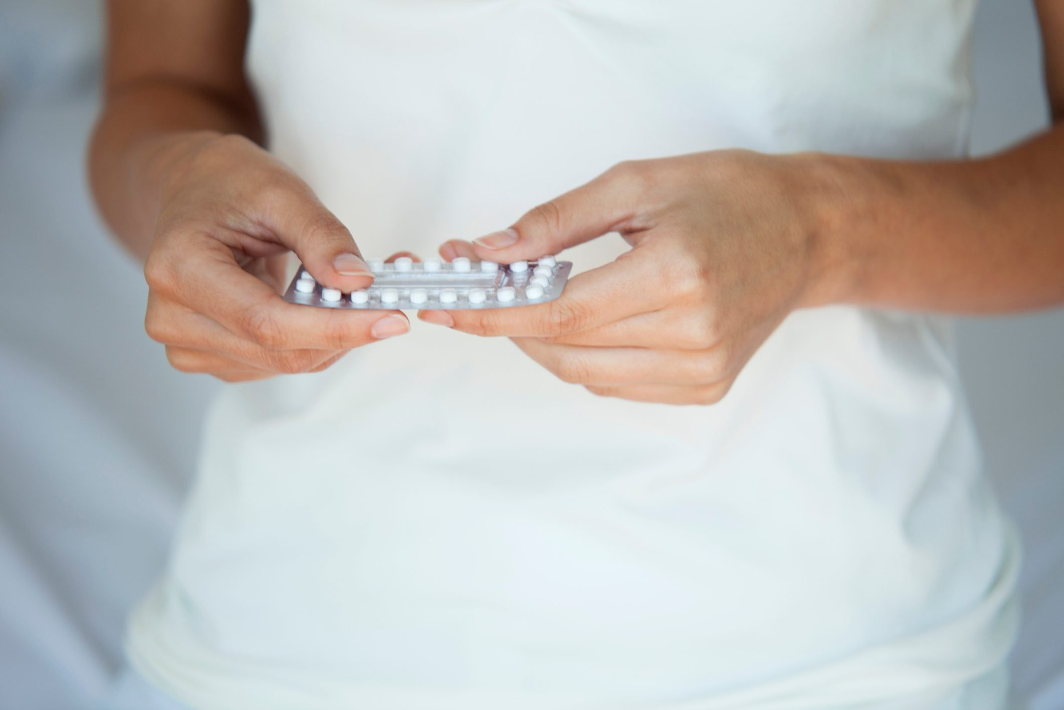 woman holding pack of birth control pills cropped close up shot